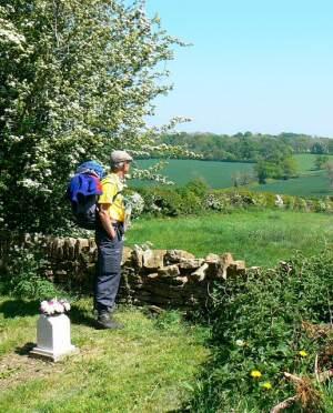A walker takes a break in the churchyard, Buckland Dinham